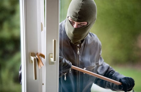 Burglar breaking into a property with a crowbar